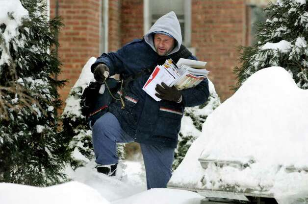 Letter carrier Armand Corlew Jr. steps over a snow drift on his way to the next home on his route following a snow storm on Wednesday, Feb. 2, 2011, in Albany. Corlew said he's been dealing with the work - and the weather - for 13 years. (Cindy Schultz / Times Union) Photo: Cindy Schultz