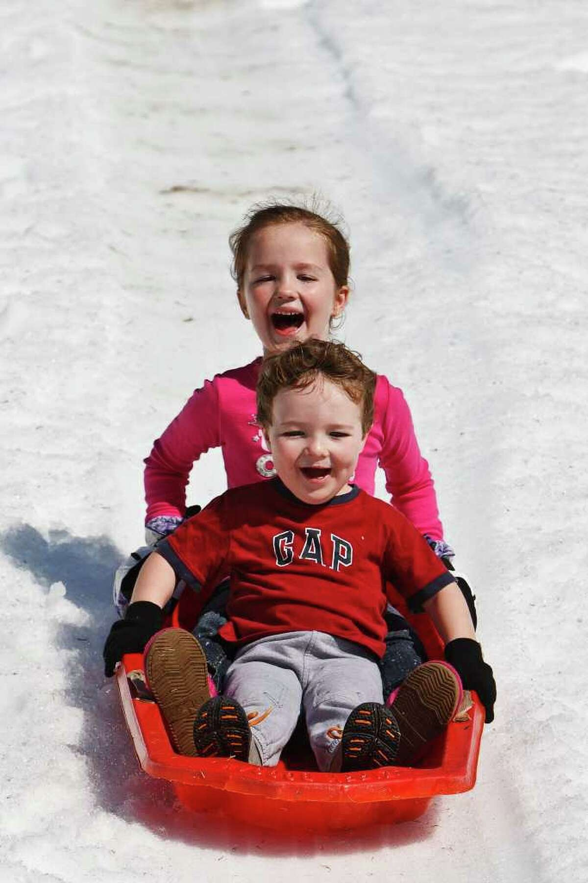 Stone Fitch (3) and his sister Sophia (6) ride a sled down the Pure Party Ice Snow Slide during the Castle Hill's Homeowners Association's 4th annual Snow Day at the Commons of Castle Hills on Jan. 30, 2011. Photo by Marvin Pfeiffer