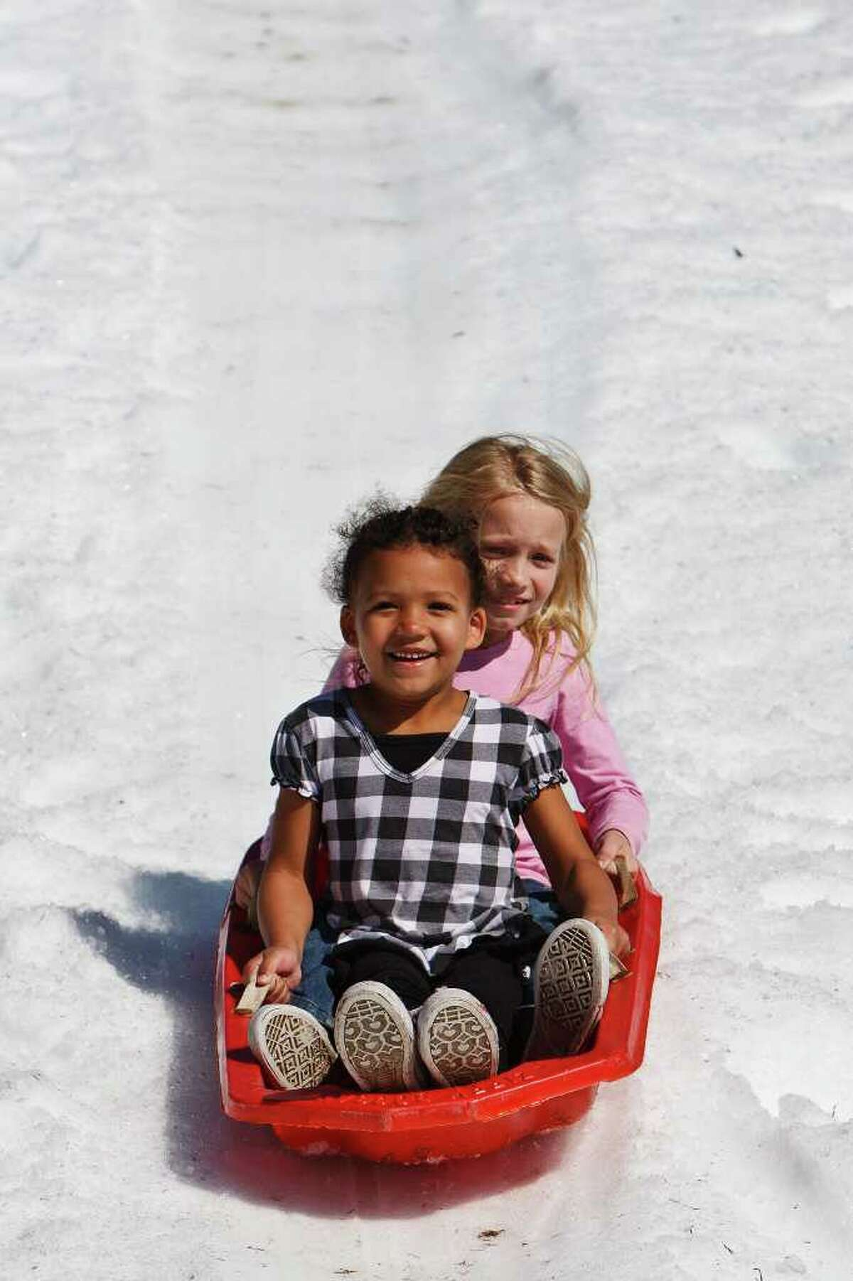 Monica Brooks (5) and Melissa Brooks (7) ride a sled down the Pure Party Ice Snow Slide during the Castle Hill's Homeowners Association's 4th annual Snow Day at the Commons of Castle Hills on Jan. 30, 2011. Photo by Marvin Pfeiffer