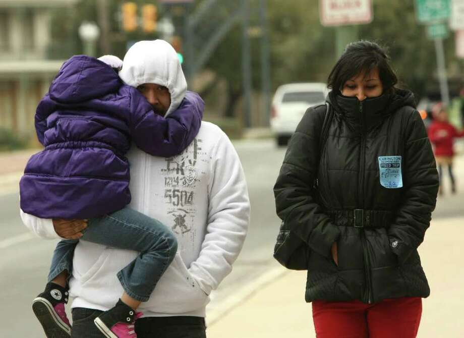 METRO:  Jose and Lillian Reveles and their daughter Princess, 6, try to stay warm as they walk along Nueva St on Wednesday Feb. 2, 20100. Temperatures dropped into the teens and are expected to stay below freezing.  HELEN L. MONTOYA/hmontoya@express-news.net Photo: HELEN L. MONTOYA, SAN ANTONIO EXPRESS-NEWS / hmontoya@express-news.net
