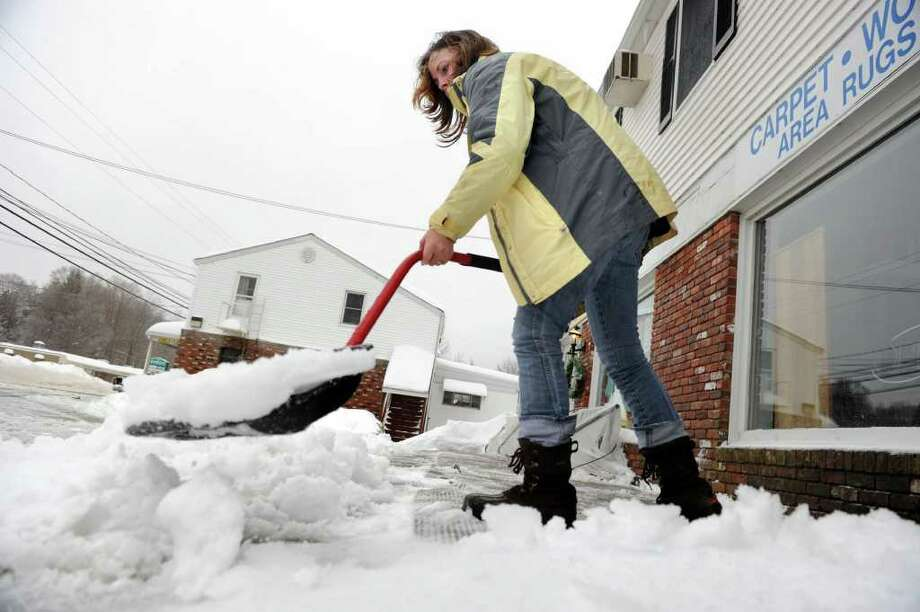 Linda Villafano, owner of The Bicycle Goodie Shop on Route 6 in Stony Hill, shovels the ice from the front of her shop Wedneday morning, February 2, 2011. Photo: Carol Kaliff / The News-Times
