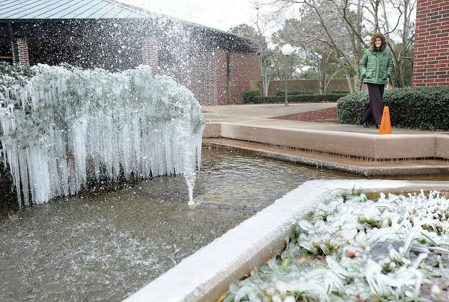Sub-freezing temperatures took advantage of a Lamar University fountain and entertained Melissa Hurd and many others with a dazzling ice sculpture.  Guiseppe Barranco/The Enterprise / Beaumont