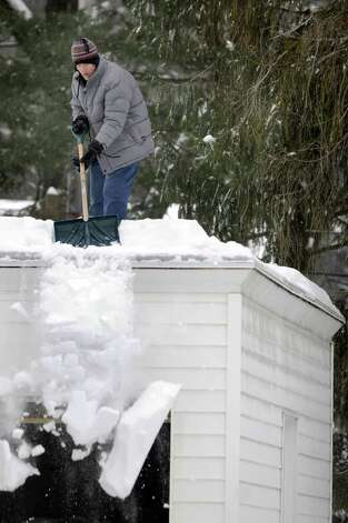 Jackson McPeters shovels snow from his garage roof following a snowstorm on Wednesday, Feb. 2, 2011, in Albany, N.Y. (Cindy Schultz / Times Union) Photo: Cindy Schultz