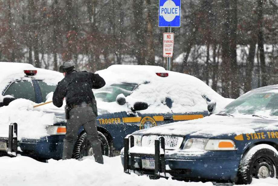 A state trooper cleans snow and ice from police cruisers at the rest stop at Exit 9 of the Northway Wednesday morning February 2, 2011.    (John Carl D'Annibale / Times Union) Photo: John Carl D'Annibale / 10011954A
