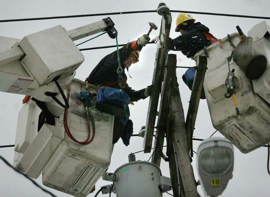 UI workers clear ice from a power pole as they replace burned wires along Central Avenue that caused a power outage in the East End of Bridgeport on Wednesday, February 2, 2011. Photo: Brian A. Pounds / Connecticut Post