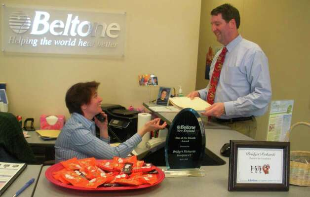 Jeffrey Weir, patient care practitioner at Beltone hearing aid center in Brookfield, works with patient care coordinator Bridget Richards. Photo: Contributed Photo/Lidia Ryan, Contributed Photo / The News-Times Contributed