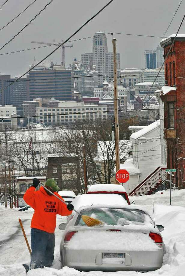 Bill Adalian of Rensselaer clears snow from his car on Harrison Avenue following Wednesday's storm in Rensselaer, NY, on Wednesday February 2, 2011.  Albany is visible in the distance, including the Alfred E. Smith building.   ( Philip Kamrass / Times Union ) Photo: Philip Kamrass