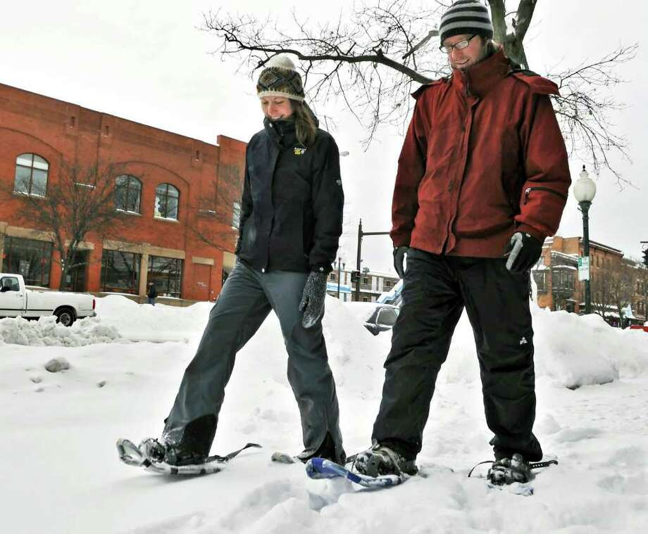Heidi Reukauf and Jamie Pisaturo, both of Saratoga Springs, snowshoe along Broadway in Saratoga Springs on their way to lunch Wednesday afternoon February 2, 2011.  Originally from Buffalo, the pair were a little disappointed in the amount of snow. (John Carl D'Annibale / Times Union) Photo: John Carl D'Annibale / 10011954A