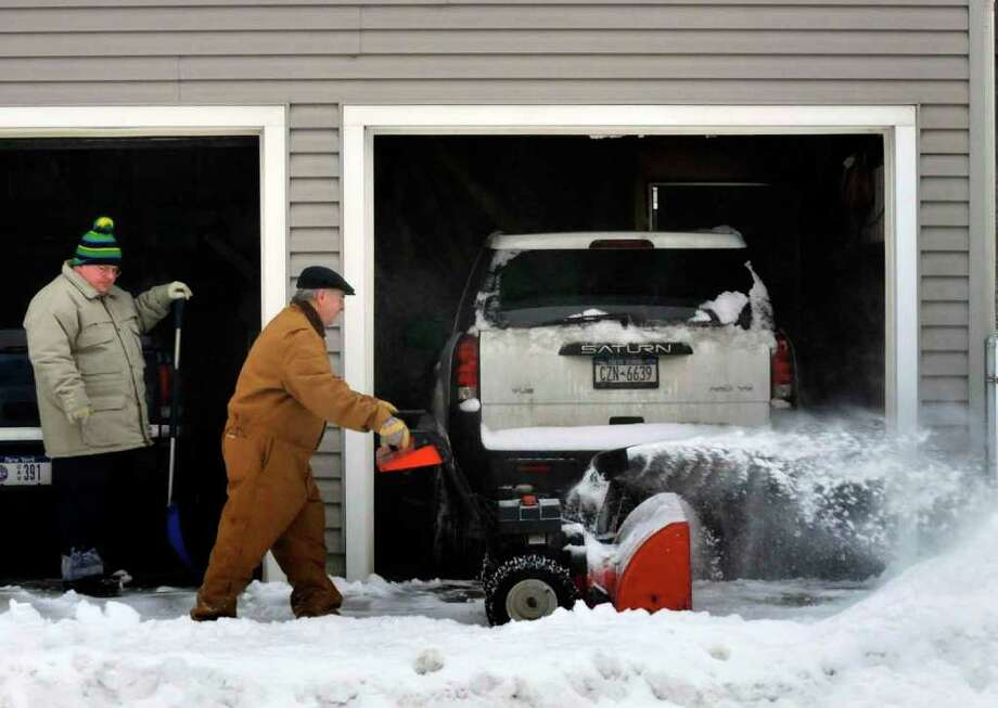 Al Sterling clears snow from the front of his garage in Green Island on Wednesday Feb. 3, 2011.( Michael P. Farrell/Times Union ) Photo: Michael P. Farrell