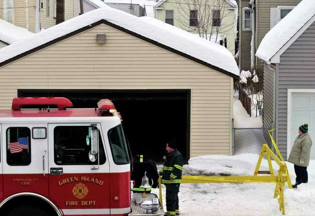 Firefighters stand watch over a garage scheduled to be demolished due to structure damage from the weight of snow on Hudson Ave in Green Island Wednesday Feb. 3, 2011.( Michael P. Farrell/Times Union ) Photo: Michael P. Farrell