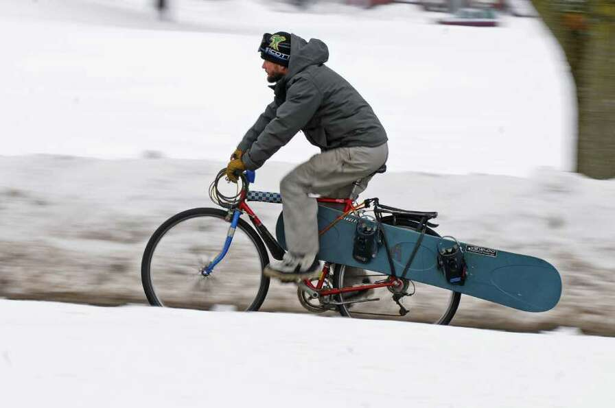 Andrew Lynn of Troy carries his snowboard on his bike while riding to meet friends near Frear Park i