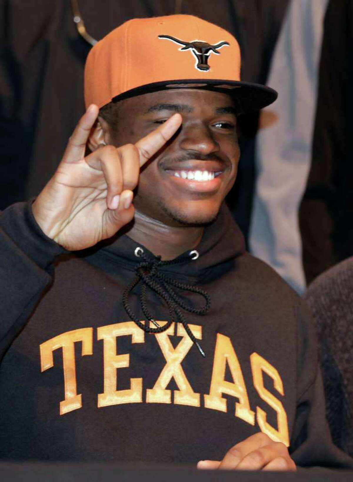 Malcolm Brown from Steele High School, flashes a big smile as he gives the horns sign after signing with The University of Texas to play football, Wednesday, Feb. 2, 2011.