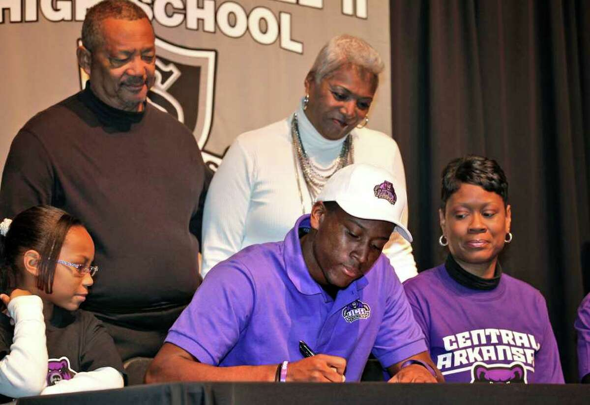 Taurean Anderson, center, from Steele High School, surrounded by family members, signs his papers with Central Arkansas, to play football, Wednesday, Feb. 2, 2011.