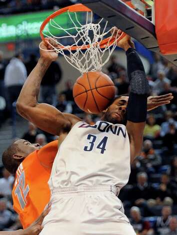 Connecticut's Alex Oriakhi dunks the ball while guarded by Syracuse's Baye Moussa Keita during the first half of an NCAA college basketball game in Hartford, Conn., Wednesday, Feb. 2, 2011. (AP Photo/Jessica Hill) Photo: AP
