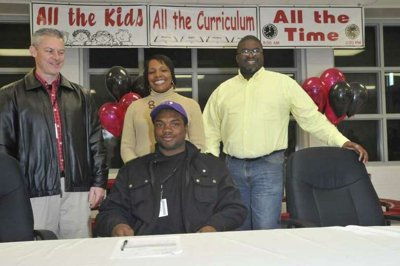 After signing with SFA, Kirbyville running back LeFredrick Ford, center, poses for the media with, f