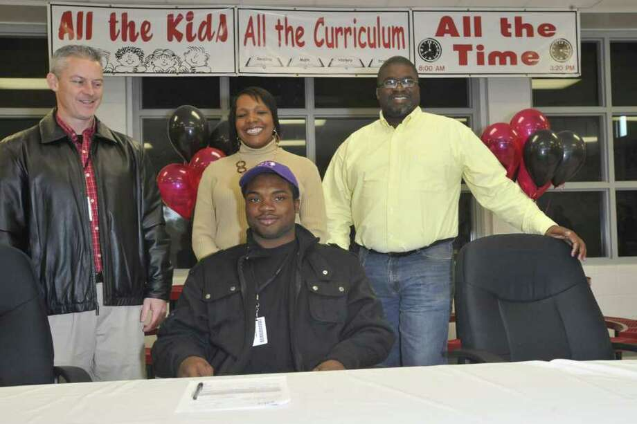After signing with SFA, Kirbyville running back LeFredrick Ford, center, poses for the media with, from left, Kirbyville interim head football coach Greg Neece, and Ford's parents, Tracy, and Freddie Samuel  during signing day at Kirbyville High School gymnasium. The 6-foot-1, 190-pound running back narrowed his list down to Lamar, Stephen F. Austin and Texas A&M before picking the Lumberjacks. He will join former Kirbyville teammate Josh Hughey at SFA.  Wednesday, February 2, 2011. Valentino Mauricio/The Enterprise Photo: Valentino Mauricio / Beaumont