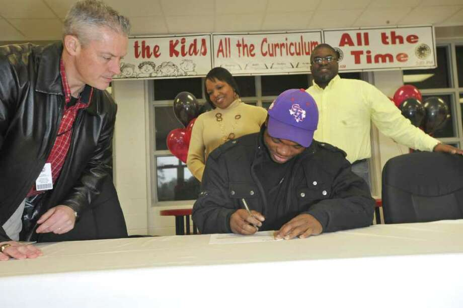 Kirbyville running back LeFredrick Ford, signs his letter of intent with Stephen F. Austin, while Kirbyville interim head football coach Greg Neece, left, and Ford's parents, Tracy, center,  and Freddie Samuel look on during signing day at Kirbyville High School gymnasium. The 6-foot-1, 190-pound running back narrowed his list down to Lamar, Stephen F. Austin and Texas A&M before picking the Lumberjacks. He will join former Kirbyville teammate Josh Hughey at SFA. Wednesday, February 2, 2011. Valentino Mauricio/The Enterprise Photo: Valentino Mauricio / Beaumont