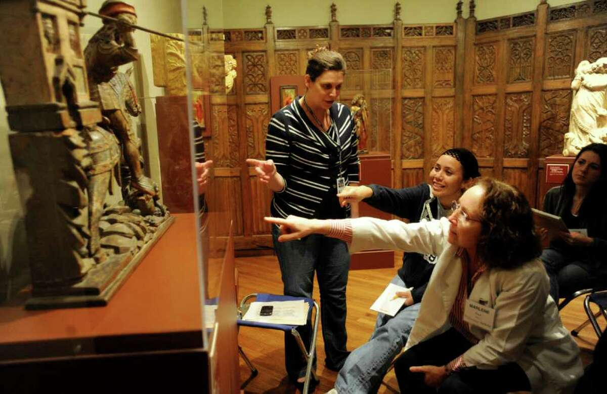 Kate Carey, director of education and teacher services of the McNay (left) explains a statue of St. George slaying a dragon to students Dawn Marie Day and Marlene Palit during a visit by the UT Health Science Center's Art Rounds program to the museum on Jan. 27.