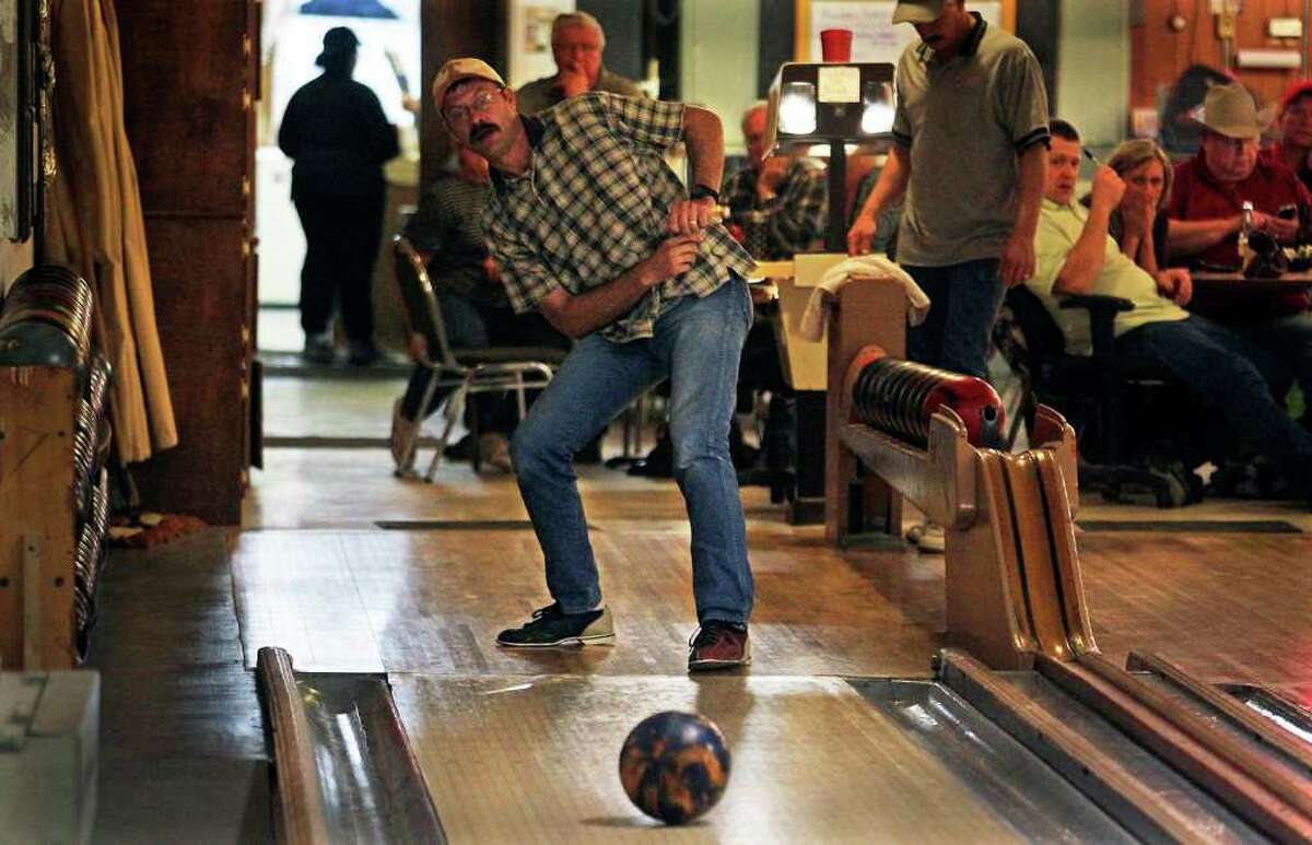 Competitors watch one of their buddies, Terrell Jonson, try a roll at the Blanco Bowling Alley Cafe.