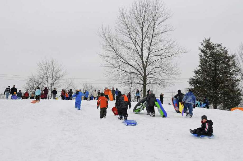 Kids take advantage of a snow day by snowboading and riding their sleds down a hill at the Tawasentha Park Winter Recreation Area in Guilderland, NY on February 2, 2011. (Lori Van Buren / Times Union) Photo: Lori Van Buren