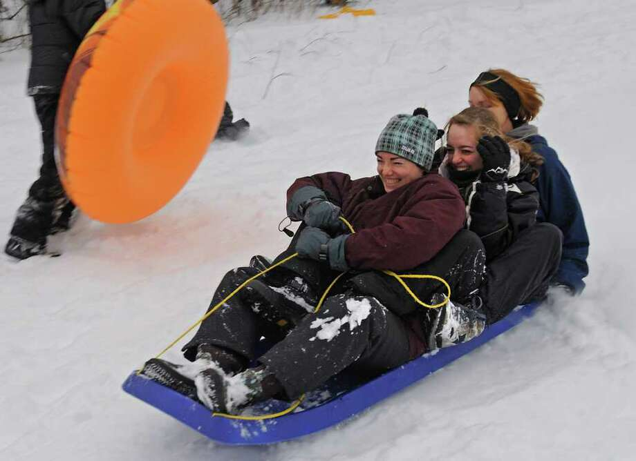 From left, Melissa Foster of Maine, Ashley Williams, age 16 of Guilderland, and her mom Amy Williams slide down a hill at the Tawasentha Park Winter Recreation Area in Guilderland, NY on February 2, 2011. Melissa was visiting the Williams family. (Lori Van Buren / Times Union) Photo: Lori Van Buren