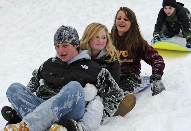 From left, Rico Rattibulli, Kennedy Lawton and Athena Damico, all age 14 of Colonie, are followed by Evan Williams, 8, of Guilderland sliding down a hill at the Tawasentha Park Winter Recreation Area in Guilderland, NY, on February 2, 2011. (Lori Van Buren / Times Union) Photo: Lori Van Buren