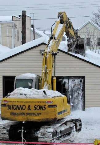 A garage owned by McNulty Funeral Home is demolished due to structural damage from the weight of snow on Hudson Ave in Green Island Wednesday Feb. 3, 2011.( Michael P. Farrell/Times Union ) Photo: Michael P. Farrell
