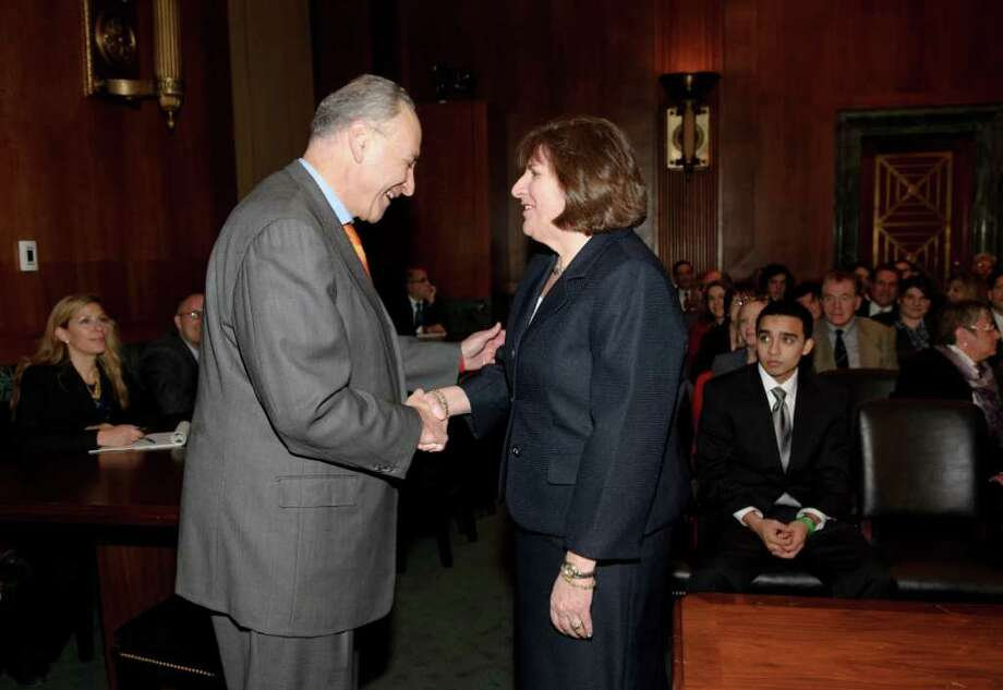 Sen. Charles Schumer greets Mae D?Agostino of Albany during her confirmation hearing in Washington, D.C., on Wednesday February 2, 2011. Schumer recommended D'Agostino to serve on the United States District Court for the Northern District of New York. Seated at right is D'Agostino's son Ted. (Joy Holder / U.S. Senate) Photo: U.S. Senate Photographic Studio- Joy Holder
