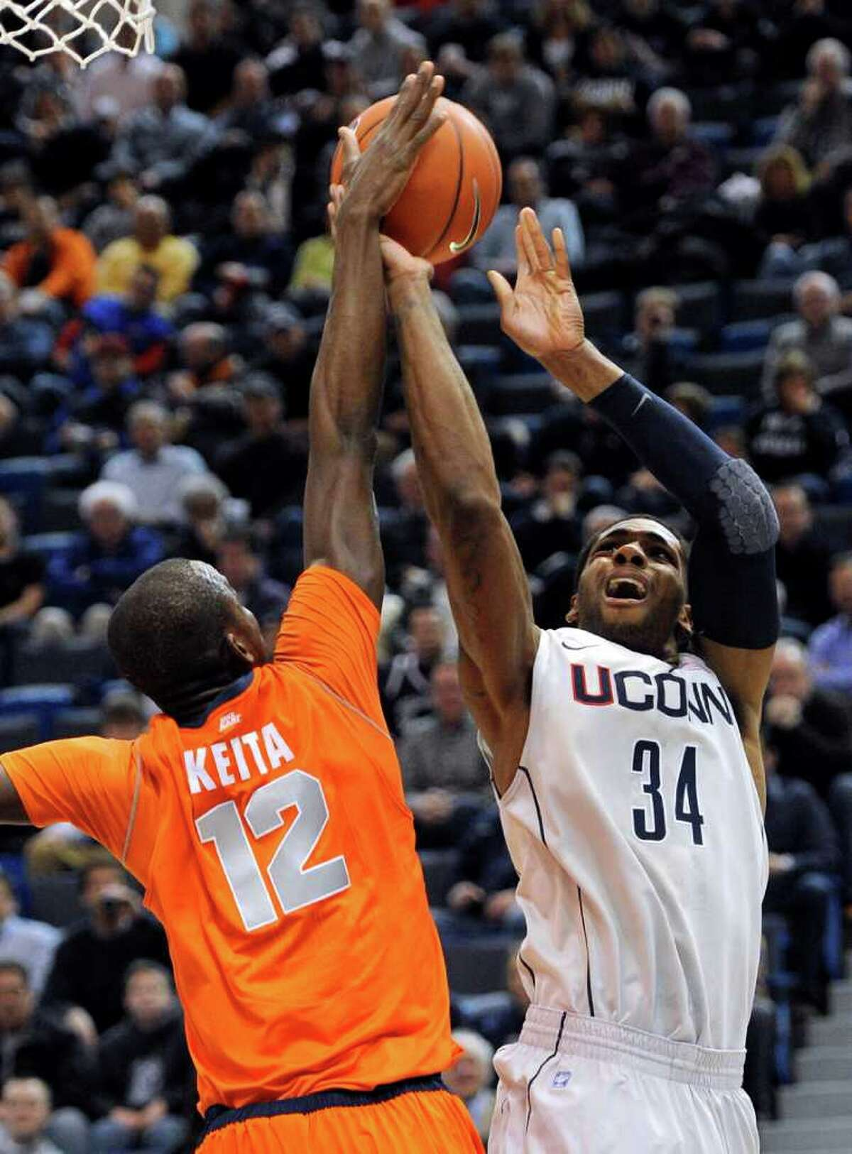 Syracuse's Baye Moussa Keita (12) blocks a shot attempt by Connecticut's Alex Oriakhi during the first half of an NCAA college basketball game in Hartford, Conn., Wednesday, Feb. 2, 2011. (AP Photo/Jessica Hill)