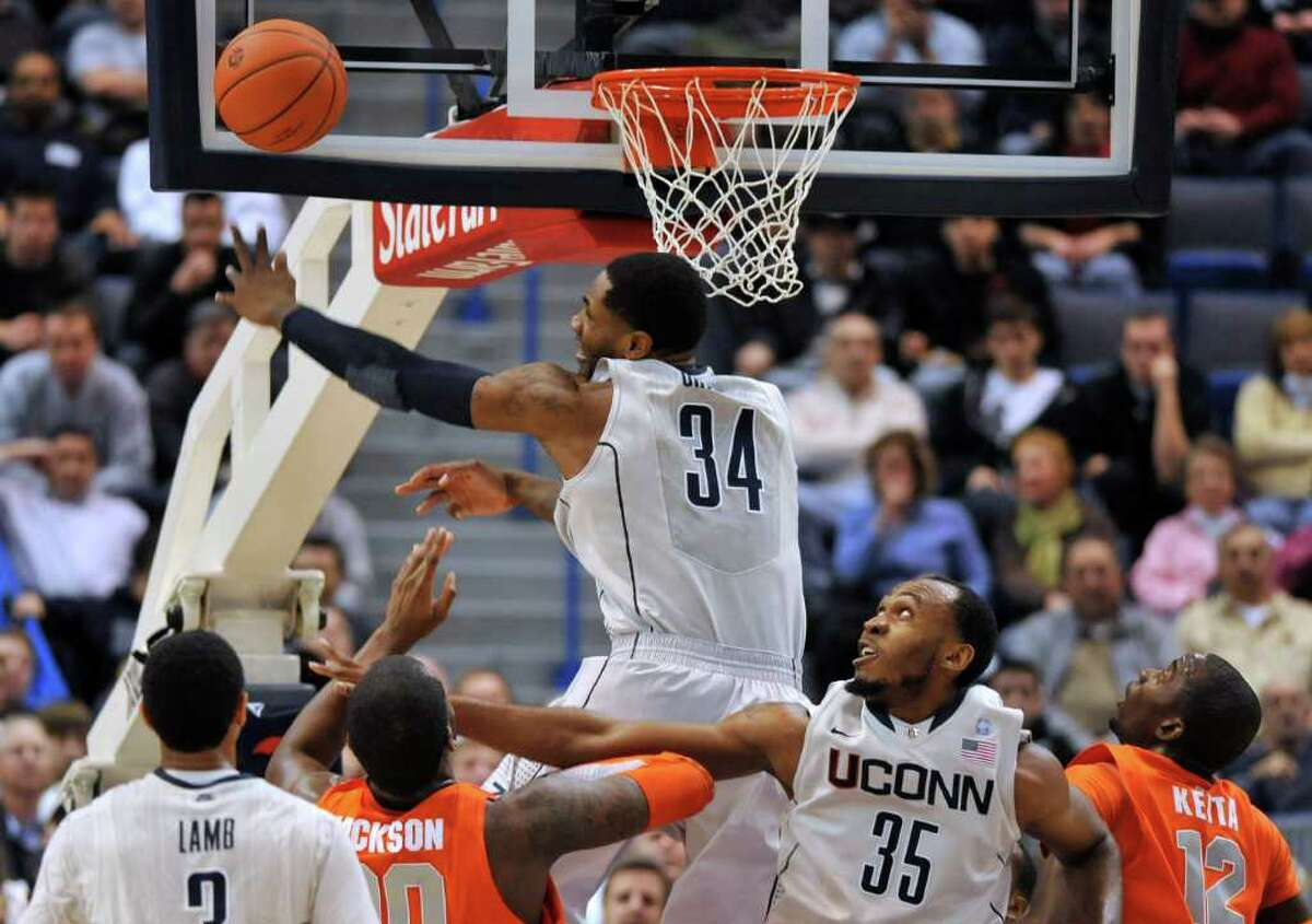 Connecticut's Alex Oriakhi (34) blocks a shot by Syracuse's Rick Jackson, second from left, as Connecticut's Charles Okwandu (35) defends during the first half of an NCAA college basketball game in Hartford, Conn., Wednesday, Feb. 2, 2011. (AP Photo/Jessica Hill)