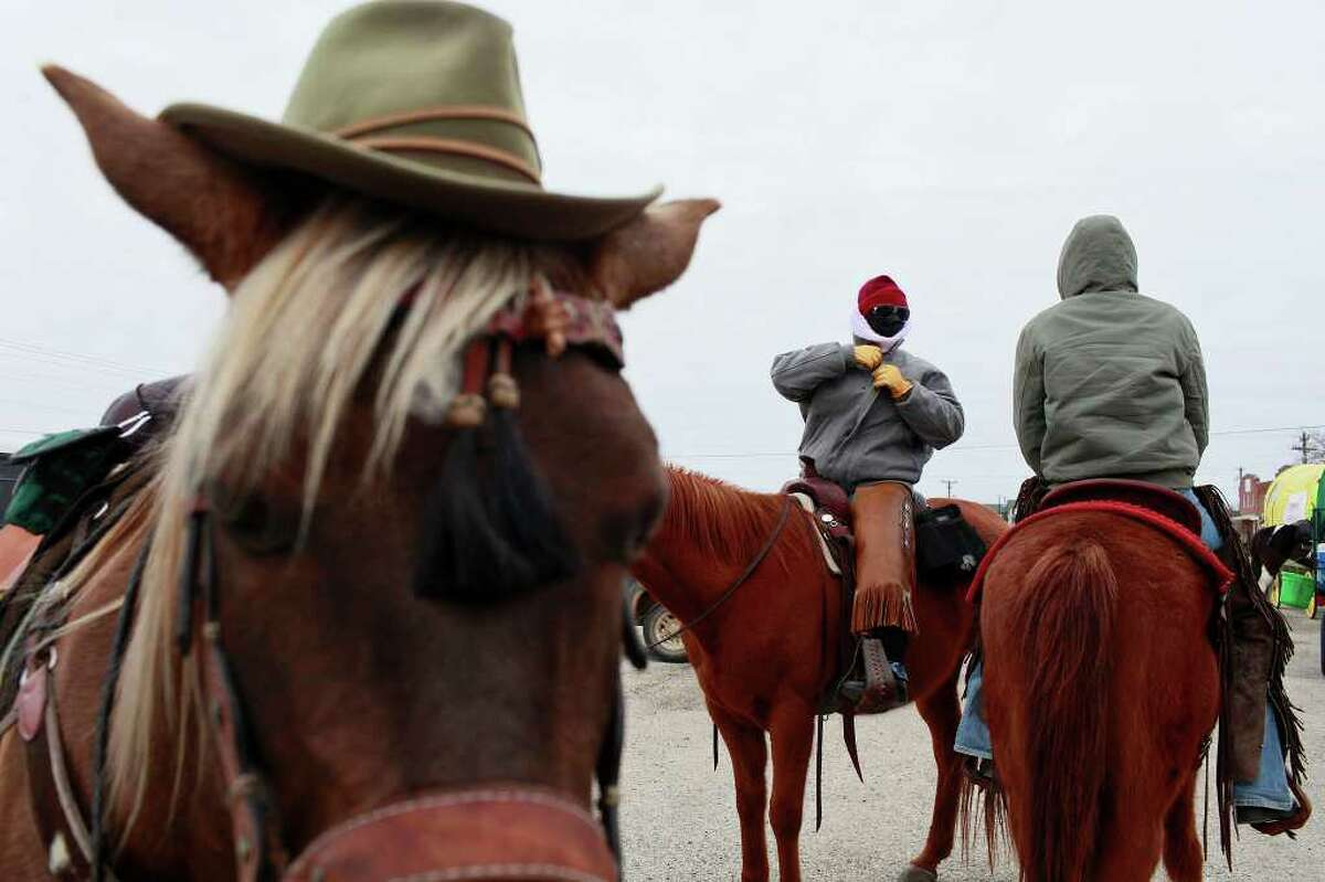 Rocky Mountain, left, sports a hat while June Lozano, center, of Floresville and Terri Byle of San Antonio get ready to hit the road again after taking a break with the South Texas Trail Riders, Inc. 52nd Annual Trail Ride to the San Antonio Stock Show and Rodeo on 181 towards Floresville on Wednesday, Feb. 2, 2011. Rick Templemire of Pilot Grove, MO, not pictured, rides Rocky Mountain. LISA KRANTZ/lkrantz@express-news.net