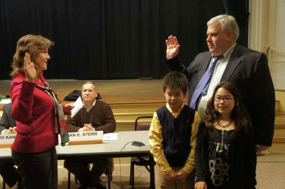 New Board of Finance member Tom Lasersohn is sworn in Wednesday, Feb. 2, 2011 by Town Clerk Patty Strauss. Standing with Lasersohn are his children, Tommy and Catey. Photo: Paul Schott / Westport News