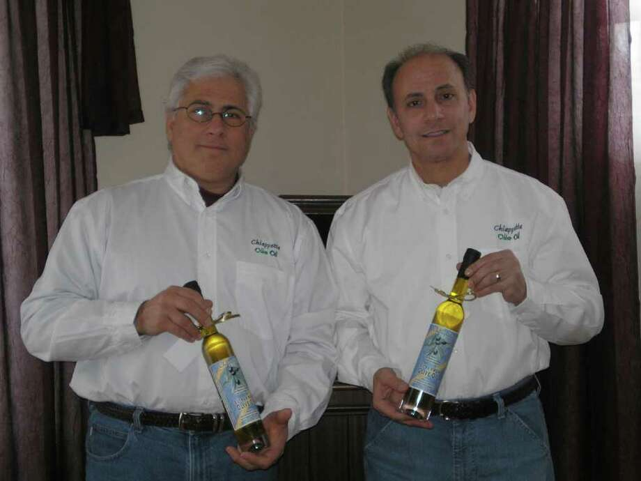 Pat Chiappetta, left, and Frank Chiapetta display samples of their family's olive oil. Photo: Contributed Photo / Norwalk Citizen