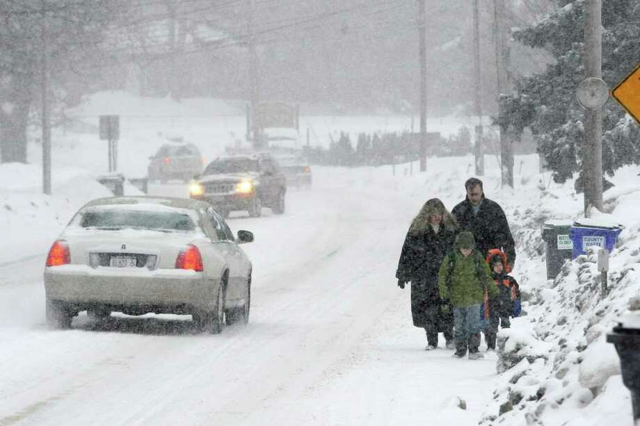 Walking to catch the school bus on Osborne Road in Colonie are the Bachman family R.J., front, Logan, Rhonda and Steven. (Skip Dickstein / Times Union) Photo: SKIP DICKSTEIN / 2008