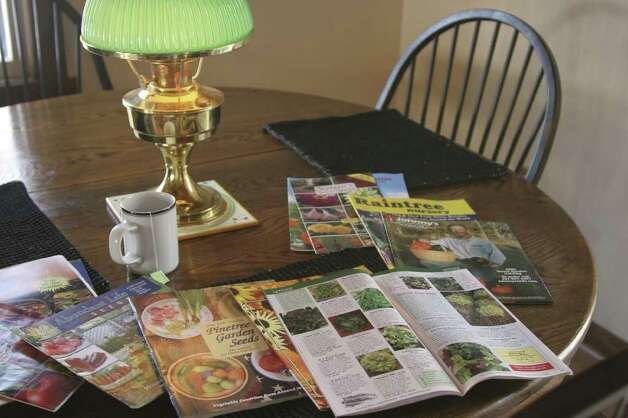 This undated file photo shows a kitchen table with a variety of seed catalogs in New Market, Va. A good activity for a snow day is to start ordering seeds and plants for your spring garden. (AP Photo/ Dean Fosdick, FILE)