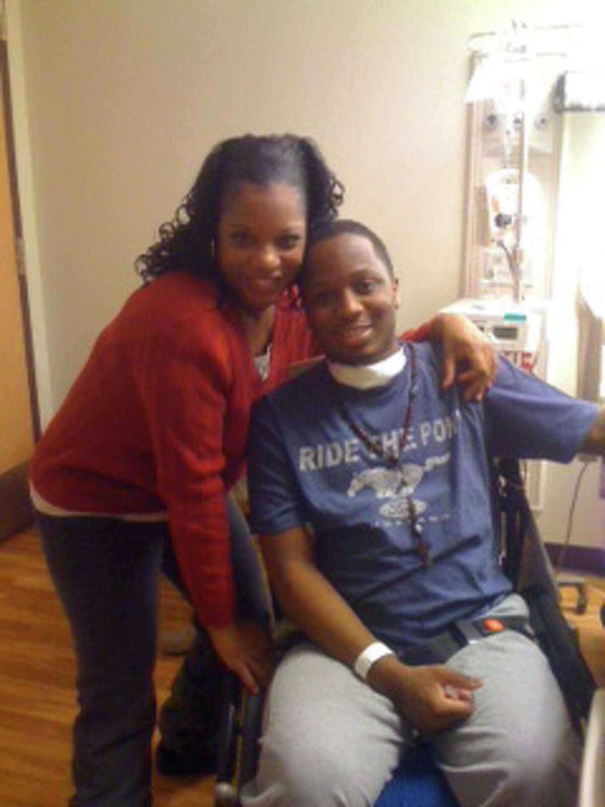 Davida Lara and her half-brother, Jamel Sawyer pose in a hospital room during Jamel's recovery. Sawyer was paralyzed after an infection by the superbug MRSA and family and friends are now trying to raise money to outfit Lara's home to accommodate a wheelchair.