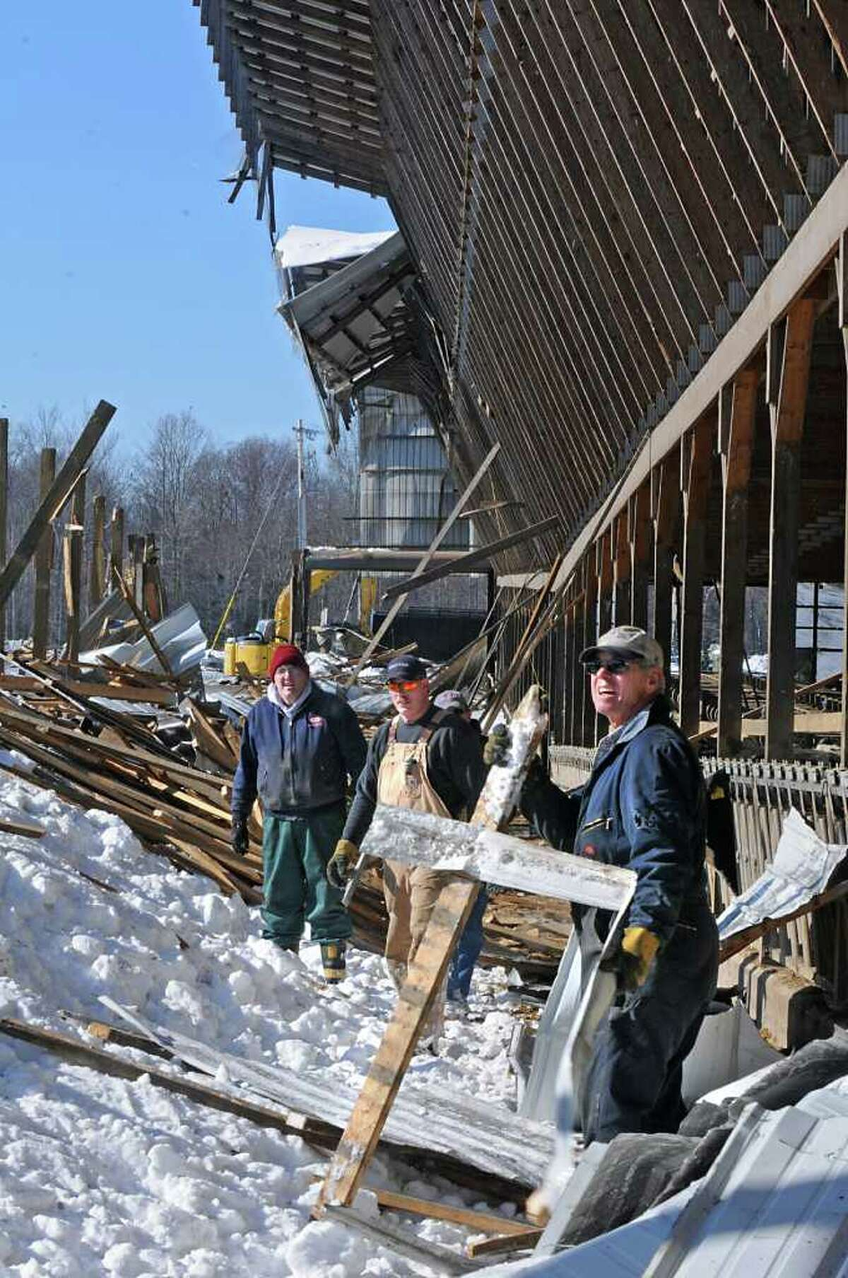 A farmhand moves a piece of debris while cleaning up after a barn roof collapsed in Northumberland killing or injuring more than 70 cows. (Lori Van Buren / Times Union)