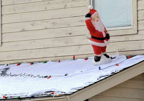 A Santa Claus figure atop a porch off of Ralph Fair Road stands amid snow after a cold front blew through the area, sprinkling snow north of San Antonio. Dec. 10, 2008. BILLY CALZADA / gcalzada@express-news.net Photo: BILLY CALZADA, SAN ANTONIO EXPRESS-NEWS / gcalzada@express-news.net