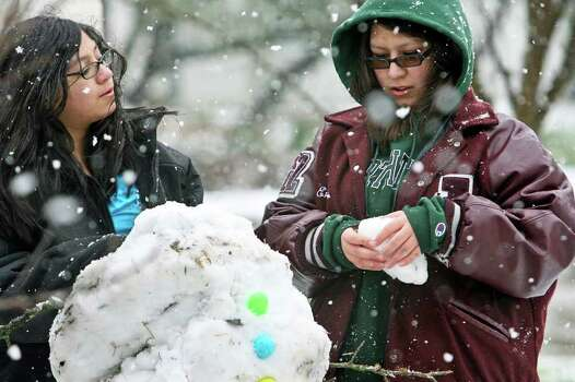 Emily Vasquez, right, takes advantage of the snow day off for schools in Johnson City, Texas, Tuesday, Feb. 23, 2010, by making a snowman with her sister Jenna Vasquez as snow continues to fall. (AP Photo/San Antonio Express-News, Tom Reel) SAN ANTONIO OUT. Photo: AP