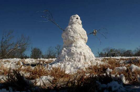 METRO- A snowwoman made by David Suarez, his wife, Rosie, and their daughters, Sarah, 12, and Angel, 23, of San Antonio, stands on State Highway 16 just north of Tilden, TX on Saturday, December 25, 2004. Lisa Krantz/STAFF Photo: LISA KRANTZ, SAN ANTONIO EXPRESS-NEWS / SAN ANTONIO EXPRESS-NEWS