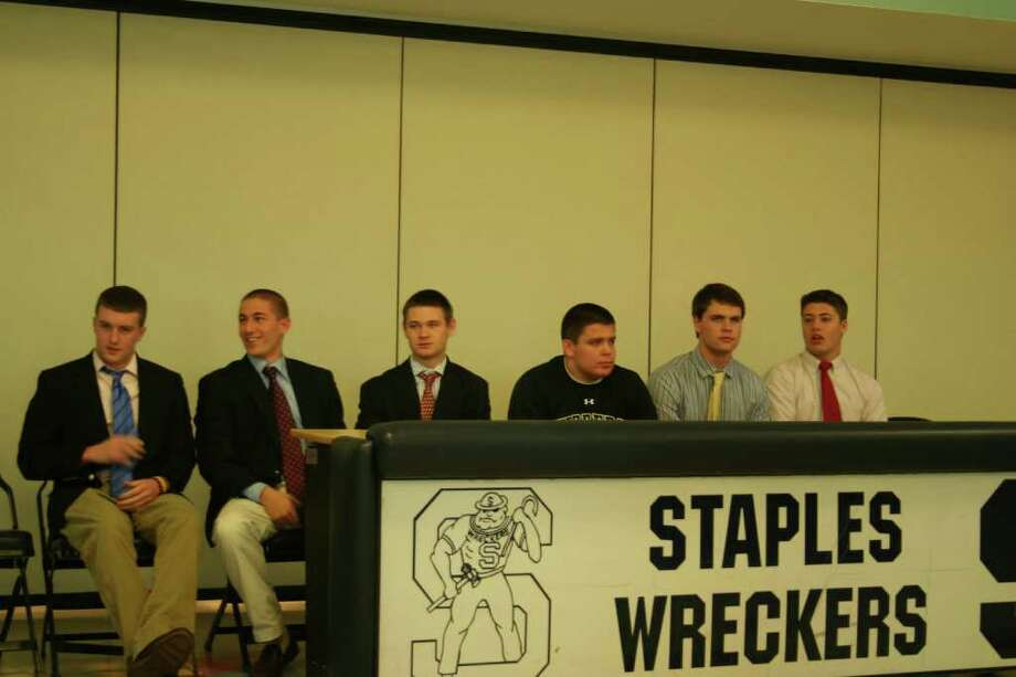 From left, Staples boys soccer players Brendan Lesch (Notre Dame), Frankie Bergonzi (Colgate) and Greg Gudis (Columbia), and football players Mike Nicklas (Wofford), Chris Coyne (Yale) and Patrick Murray (Yale) sign their letters of intent on Thursday to play Division I college sports. Sean Gallagher, who is playing soccer for Navy, is missing from the photo because the FCIAC indoor track championships took place at the same time of the signings. Photo: Contributed Photo