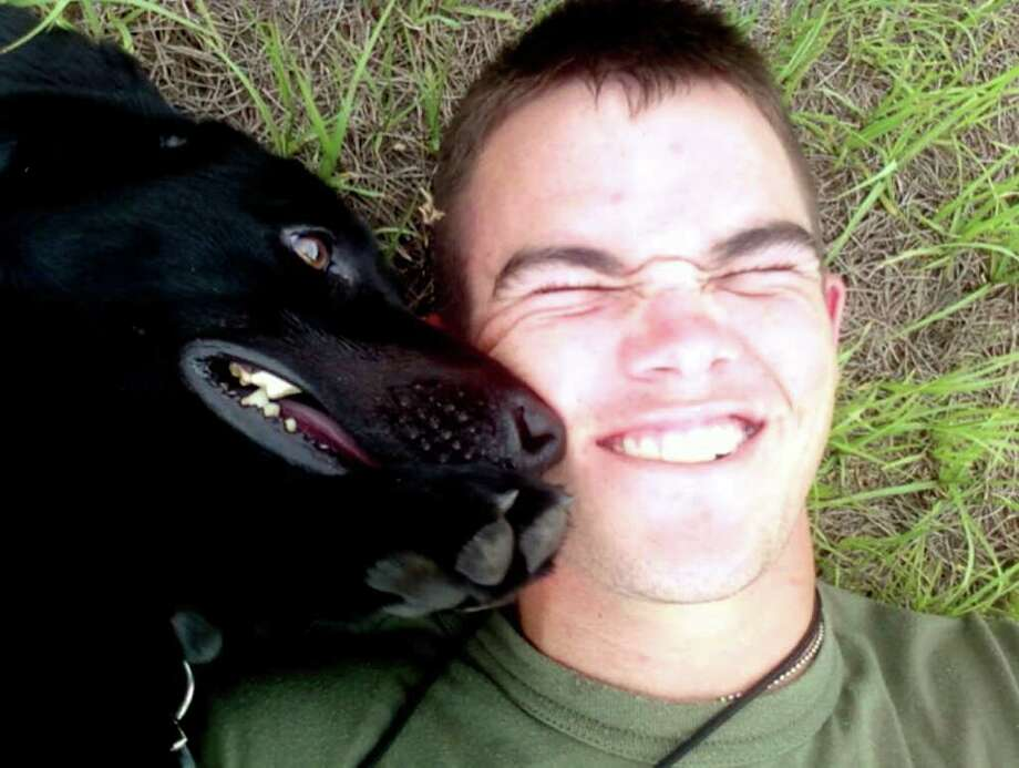 This photo shows Pfc. Colton Rusk with Eli, a black Labrador that worked sniffing out bombs for the Marine Corps. Other Marines say that during the battle in which Rusk was killed, Eli crawled on top of him to shield him. Photo: Courtesy Photo