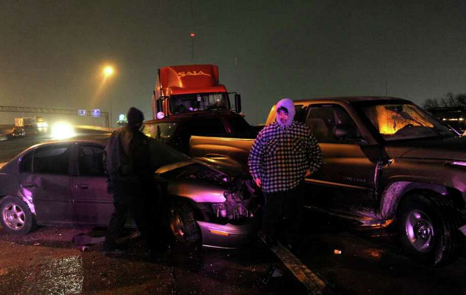 People involved in a weather-related wreck on Interstate 10 east near Fredericksburg Road inspect the wreckage. Photo: BILLY CALZADA, SAN ANTONIO EXPRESS-NEWS / gcalzada@express-news.net