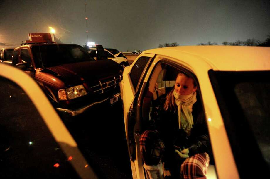 People involved in a weather-related wreck on Interstate 10 east near Fredericksburg Road sit and wait for help on Thursday night. Photo: BILLY CALZADA, SAN ANTONIO EXPRESS-NEWS / gcalzada@express-news.net