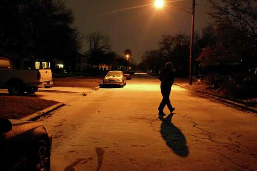 METRO - Azucena Flores walks across the street to take a photograph of the snow in San Antonio early Friday, Feb. 4, 2011. LISA KRANTZ/lkrantz@express-news.net Photo: LISA KRANTZ, SAN ANTONIO EXPRESS-NEWS / SAN ANTONIO EXPRESS-NEWS
