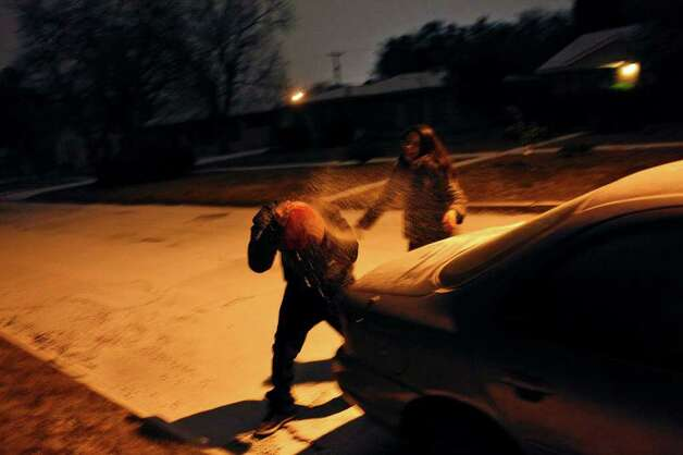 METRO - Monica Flores throws a handful of snow that she scooped off the car to throw at her boyfriend, Jose Flores (no relation) in San Antonio early Friday, Feb. 4, 2011. LISA KRANTZ/lkrantz@express-news.net Photo: LISA KRANTZ, SAN ANTONIO EXPRESS-NEWS / SAN ANTONIO EXPRESS-NEWS
