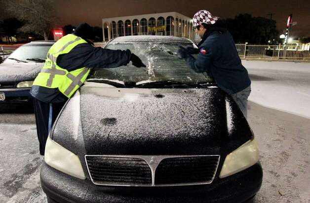 James Josey (right) and Ray Ramirez attempt to scrape snow and ice off the windshield of Josey's car at the H-E-B parking lot near Wurzbach and IH-10 Snow in the early morning hours of Friday, Feb. 4, 2011. Snow and ice descended upon San Antonio in the city's first snow event of the year. Kin Man Hui/kmhui@express-news.net Photo: KIN MAN HUI, SAN ANTONIO EXPRESS-NEWS / San Antonio Express-News