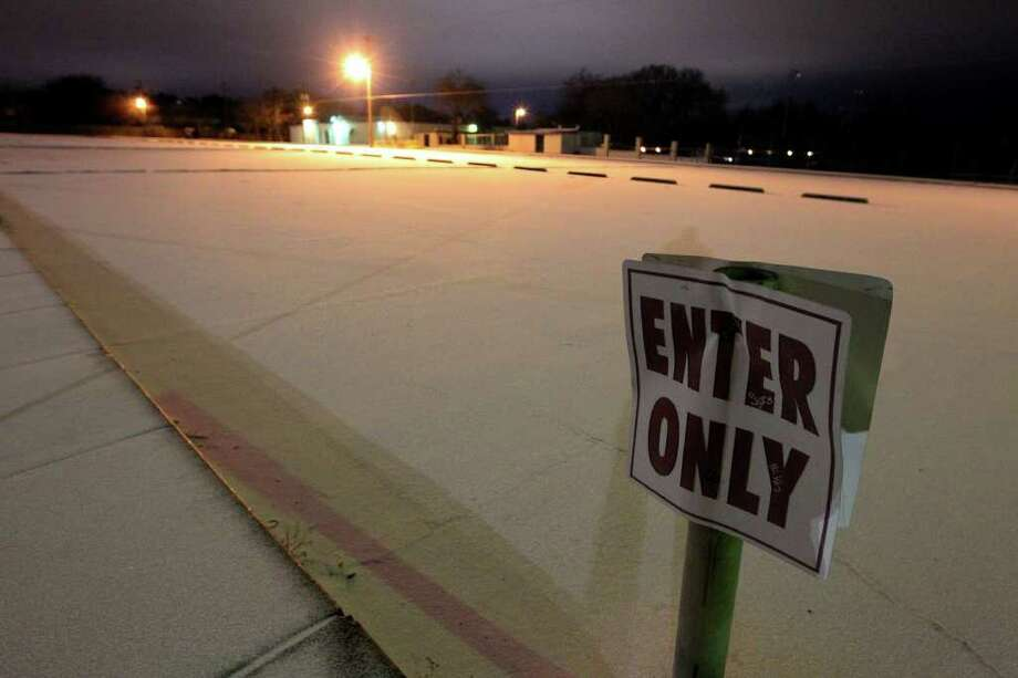 Snow covers an empty parking lot of Colonies House along Colony Drive in San Antonio during the early morning hours of Friday, Feb. 4, 2011. Kin Man Hui/kmhui@express-news.net Photo: KIN MAN HUI, SAN ANTONIO EXPRESS-NEWS / San Antonio Express-News