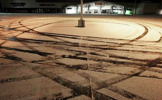 Swirls from a vehicle driving in a snow-covered parking lot is seen during the year's first snow event in San Antonio in the earlying morning hours of Friday, Feb. 4, 2011. Kin Man Hui/kmhui@express-news.net Photo: KIN MAN HUI, SAN ANTONIO EXPRESS-NEWS / San Antonio Express-News