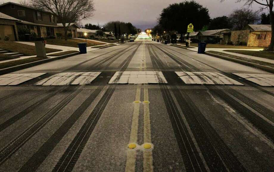 Snow and ice covers a speed bump along Colony Drive in San Antonio in the early morning hours of Friday, Feb. 4, 2011. Kin Man Hui/kmhui@express-news.net Photo: KIN MAN HUI, SAN ANTONIO EXPRESS-NEWS / San Antonio Express-News